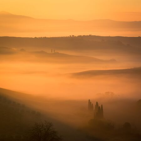 The beautiful valley in Tuscany is full with fog at this mystical sunrise at San Quirico dOrcia, Italy. Mountain peaks and ranges fill the golden picture with shadows and highlights. Square photo Stock Photo