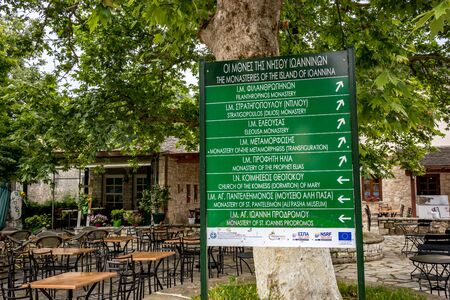 IOANNINA, GREECE - JUNE 6, 2019 - Huge green board gives tourist info in Greek and English at the Ioannina Island port on lake Pamvotida near the beautiful small Greek town. Early morning spring view
