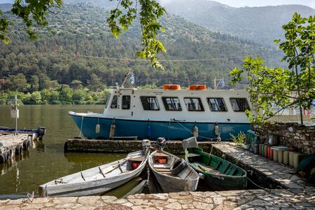 IOANNINA, GREECE - JUNE 6, 2019 - Three small old tourist cruise white and blue ferryboats moore on lake Pamvotida near the beautiful small Greek town. Early morning spring view with unusual fog