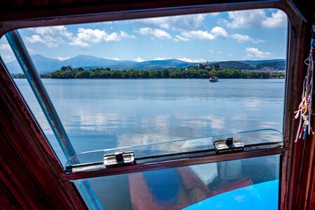 Calm and tranquil water of lake Pamvotida near the Greek town of Ioannina, early spring morning with few puffy clouds, selective focus, landscape image taken from ferry framed by boat window