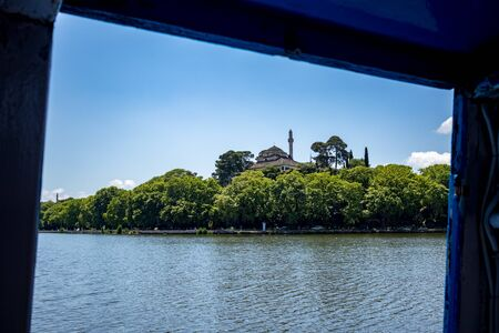 Calm and tranquil water of lake Pamvotida near the Greek town of Ioannina, early spring morning with town mosque hidden in trees, selective focus landscape image taken from ferry framed by boat window Фото со стока