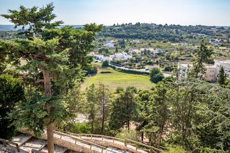 Scenic sight, street view from the beautiful town of Locorotondo, Bari province, Apulia, Puglia , Southern Italy. Panoramic green landscape over the valley close by with whitewashed houses Stock Photo