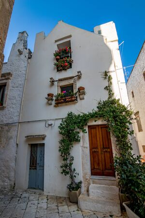 Scenic sight, street view from the beautiful town of Locorotondo, Bari province, Apulia, Puglia , Southern Italy. Medieval building whitewashed facade with green plants. Stock Photo