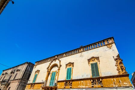 Scenic sight, street view from the beautiful town of Locorotondo, Bari province, Apulia, Puglia , Southern Italy. Old buildings fronts on the central street