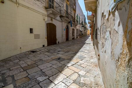 LOCOROTONDO, ITALY - AUGUST 28, 2018 - Locorotondo in Puglia, Apulia region, Southern Italy is a small town with amazing architecture, narrow streets and warm atmosphere. Narrow street, scoured patio