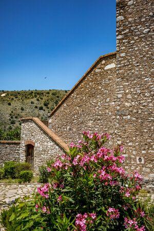 Turmtreppe, verschwommene Blumen. Schöner warmer Frühlingstag und archäologische Ruinen im Nationalpark Butrint, Albanien, UNESCO-Erbe. Reisefotografie mit frischer grüner Flora und strahlend blauem Himmel