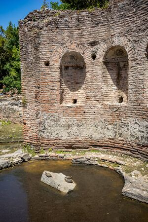 Building ruins with water turtles under sunlight. Beautiful warm spring day and archeological ruins at Butrint National Park, Albania, UNESCO heritage. Travel photography with fresh green flora