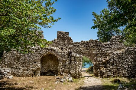 Building ruins with arched entrance. Beautiful warm spring day and archeological ruins at Butrint National Park, Albania, UNESCO heritage. Travel photography with fresh green flora