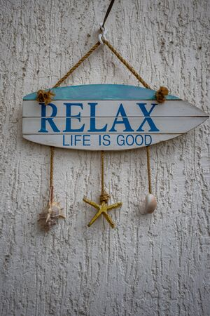 Boat shaped wooden home board sign saying Relax, life is good. Positive thinking concept, hanging on white wall with three sea shells on strings