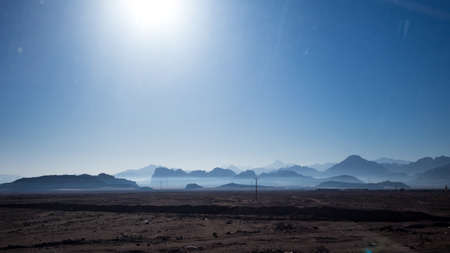 Jordan in winter, desert Uadi Rum or Wadi Rum or Valley of Moon, scenery cloudless blue sky landscape view at the end of January. Travelling in the beautiful Middle East kingdom. Sand and rocks