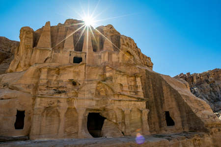 Petra, Jordan. Stunning sunlight rays, light diffraction effect over the Obelisk Tomb or Bab As Siq Triclinium in the beautiful Middle East kingdom. Cloudless clear blue sky warm winter day