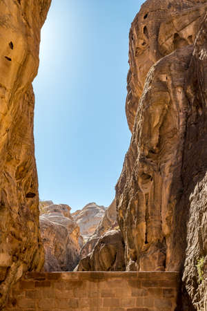 Breathtaking natural gorge called Al-Siq, carved in the red cliffs by the water flow, Petra ancient city complex and tourist attraction, Hashemite Kingdom of Jordan. Sunny winter day, cloudless sky
