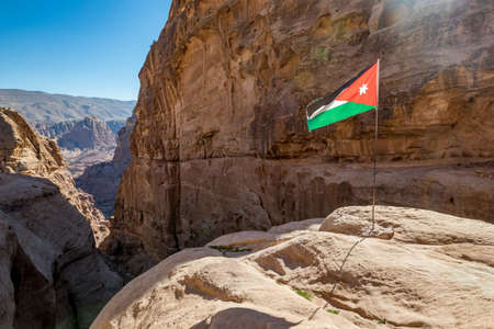 Cliffs and Jordanian flag under the sunlight. I enjoyed the amazing views from the scenery Monastery Route, beautiful sunny day at Petra complex and tourist attraction, Hashemite Kingdom of Jordan
