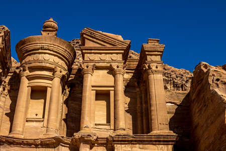 Sunny cloudless day close-up detailed view of the stunning Ad-Deir in the ancient city of Petra, Jordan. Ad-Deir or The Monastery. Petra complex and tourist attraction, Hashemite Kingdom of Jordan