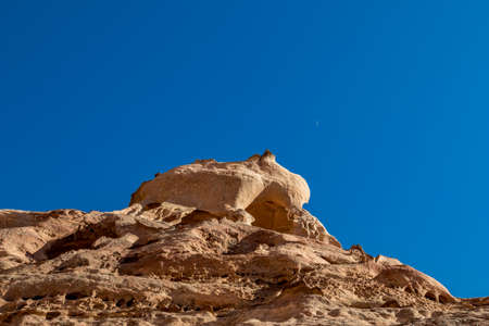 Cliff formations and partial Moon. Amazing views from the scenery Monastery Route, beautiful sunny day at Petra complex and tourist attraction, Hashemite Kingdom of Jordan