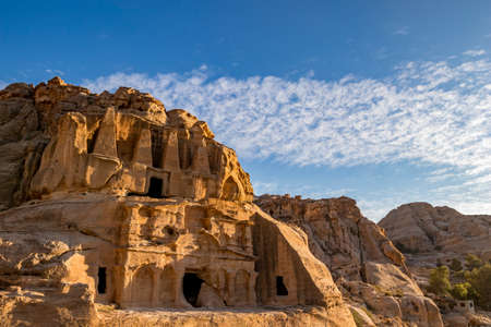 Petra, Jordan. Setting sun light over the Obelisk Tomb or Bab As Siq Triclinium in the beautiful Middle East kingdom. Beautiful clouds in the blue sky warm winter day afternoon