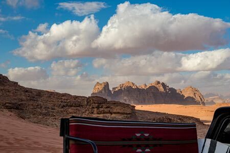 Jordan, Wadi Rum desert, winter day landscape with white puffy clouds. Beautiful desert could be explored on safari. Blurred bench in foreground on pickup SUV truck covered with rug for tourists.