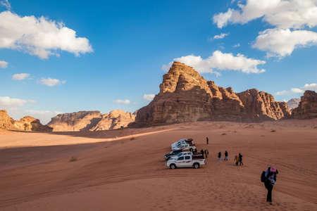 WADI RUM, JORDAN - JANUARY 31, 2020: Few safari SUVs waiting for tourist who enjoy walk on the red sand. Winter puffy clouds windy afternoon sky. beautiful desert, Hashemite Kingdom of Jordan