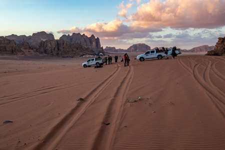 WADI RUM, JORDAN - JANUARY 31, 2020: Few tourists wait for sunset near safari SUVs on the red sand. Winter puffy clouds windy afternoon sky. beautiful desert, Hashemite Kingdom of Jordan