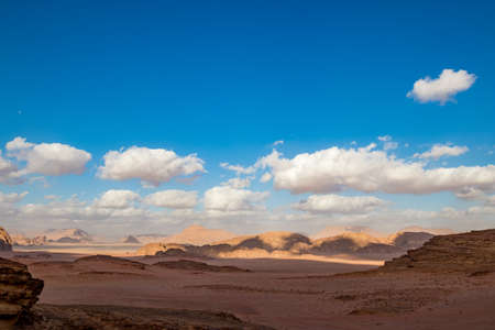 Kingdom of Jordan, Wadi Rum desert, sunny winter day scenery landscape with white puffy clouds and warm colors. Lovely travel photography. Beautiful desert could be explored on safari. Colorful image 版權商用圖片