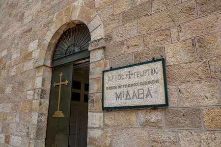The beautiful mosaic plaque at the entrance of Saint George Greek orthodox church in Madaba, Jordan. Winter day street view with the open old door of the religious building 版權商用圖片