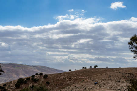 Minimalistic view, landscape, Promised Land hill as seen from Mount Nebo, Kingdom of Jordan, Middle East, beautiful clouds in windy winter afternoon