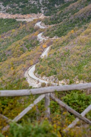 Curvy mountain empty road, Xanthi region, Northern Greece. High angle view, late autumn hazy day, travel photography. Blurred wooden fence in the foreground