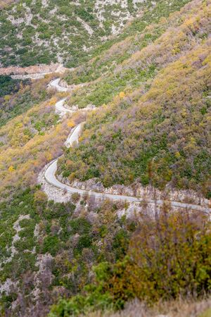 Curvy mountain empty road, Xanthi region, Northern Greece. High angle view, late autumn hazy day, travel photography