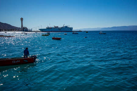 Aqaba, Jordan - February 2, 2020: Fisherman gets back to land in small motor boat after fishing in Red Sea. Big cruise ship in background. Cloudless clear sky winter day. Horizontal frame 新聞圖片