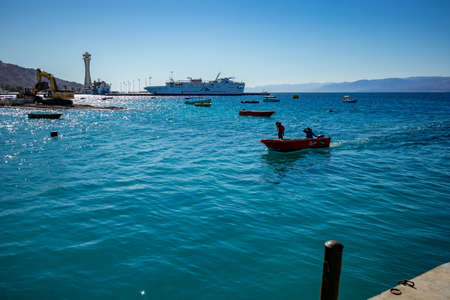 Aqaba, Jordan - February 2, 2020: Two fishermen get back to land in small motor boat after fishing in Red Sea. Big cruise ship in background. Cloudless clear sky winter day. Horizontal frame 新聞圖片