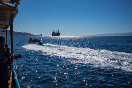 Aqaba, Jordan - February 2, 2020: Tourists enjoy views of Red Sea with glass boat tours. Cloudless clear sky winter day. Enjoying the underwater life becomes more and more popular lately