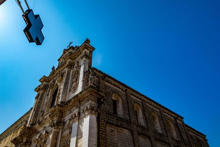 Amazing church of St. Maria, Mesagne, Puglia, Italy. Portrait mode view, clear blue sky, hot summer day, travel photography, taken from across the streets under pharmacy store cross sign
