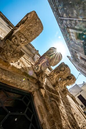 Sun rays diffraction light photo effect in alleyway on the streets of Mesagne, Puglia, Italy. Amazing ancient architectural artifacts, house decorations. Low angle street view, travel photography 版權商用圖片