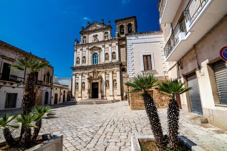The old church of St. Anna, Mesagne. Puglia, Italy under the clear blue sky of a sunny summer day, travel photography, street view with few beautiful decorative palm trees in foreground