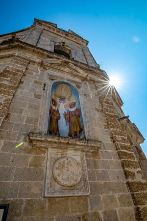 Low angle street view of Church of SS. Cosma e Damiano. Mesagne. Puglia. Italy. Beautiful sun light diffraction effect in the top right-hand corner of the frame, vertical portrait mode 版權商用圖片