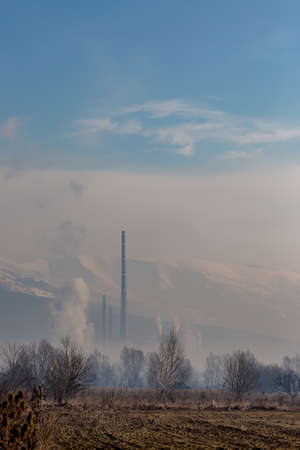 Hazy day afternoon vertical landscape with factory smoke, travel photography at the Rose Valley, Central Bulgaria. Snow slopes of Stara Planina mountain in background, pastel colors