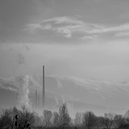 Hazy day afternoon square landscape with factory smoke, travel photography at the Rose Valley, Central Bulgaria. Snow slopes of Stara Planina mountain in background, black and white image
