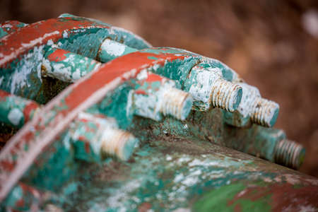 Selective extremely shallow focus close up of big nuts and bolts covered in layers of rust and old paint. Partial colorful view of round water supply pipe connection section. Natural daytime light 版權商用圖片