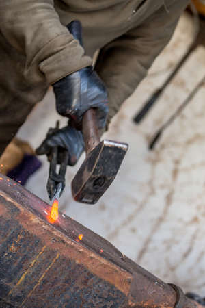 Forging red hot metal with hammer. Selective shallow focus on the melted steel, slow speed picture with motion blurred blacksmith hands and tools. Close-up diagonal view