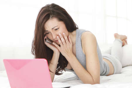Girl is crying while looking at the computer while listening conversation on the phone,  in bed photo