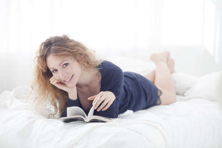 woman smiling while reading a book in her bed photo