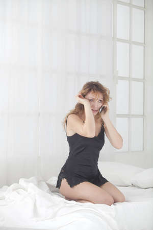 woman cry while talking on the phone , kneelink in bed with lingerie photo