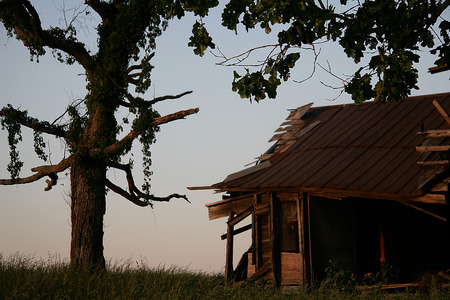 old house with half dead tree at sunset Imagens