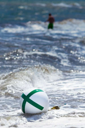 waves on a shore with buoy and single person