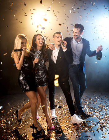 Group of happy stylish friends celebrating with champagne bottle and confetti Stock Photo