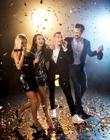 Group of happy stylish friends celebrating with champagne bottle and confetti Reklamní fotografie