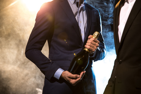 Partial view of two stylish men in suits with champagne bottle
