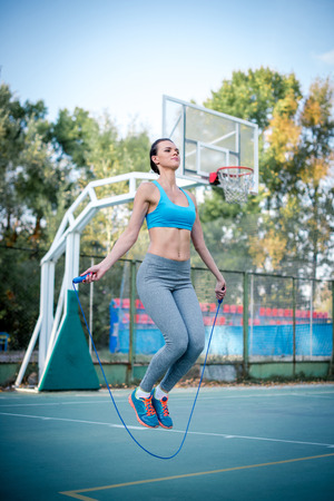 saltar la cuerda: Brunette woman skipping with a jump rope outdoors