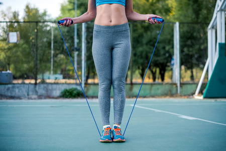 Woman in sportswear exercising with jump rope on the stadium Stock Photo