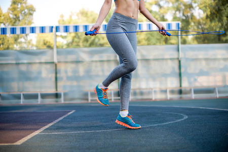 Cropped shot of woman in sportswear jumping rope at stadium Stock Photo
